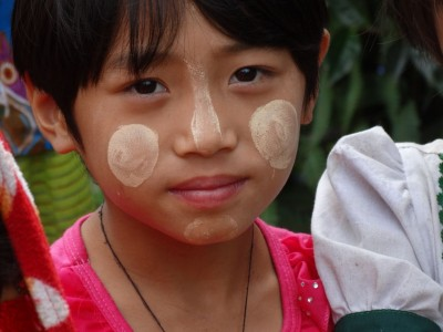 A young Lisu girl with Thanaka applied to her face in traditional fashion.
