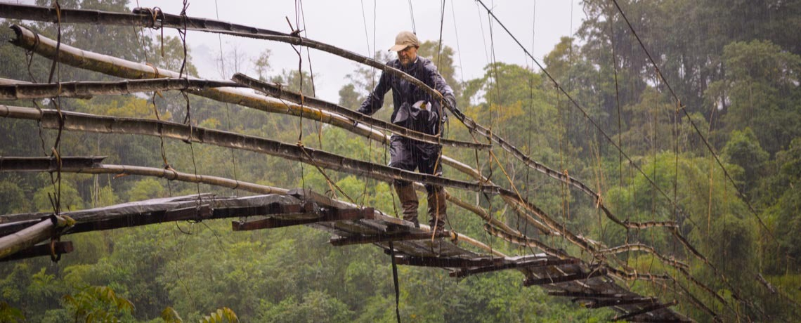 Crossing a primitive bridge in Myanmar, rain pouring down