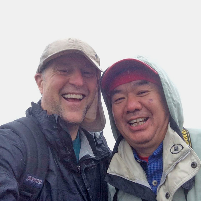 Two friends smiling on a mountaintop.